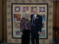 Margaret & Don Anderson pose by the amazing quilt created by daughter Karen Anderson
